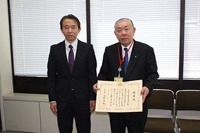 感謝状を掲げる大澤会長と石飛水道課長